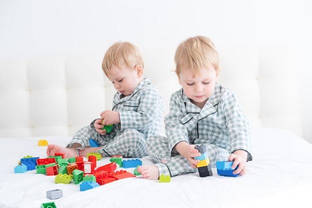 Zwei lustige jungenbrüder zwillinge auf weißem bett im pyjama spielen im konstrukteur.