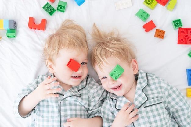 Zwei lustige jungenbrüder zwillinge, die auf weißem bett im pyjama mit buntem konstruktor liegen.