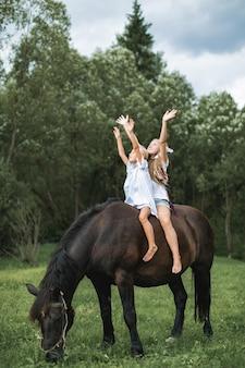 Zwei lustige kindermädchenschwesternfreunde, die ein pferd zusammen reiten