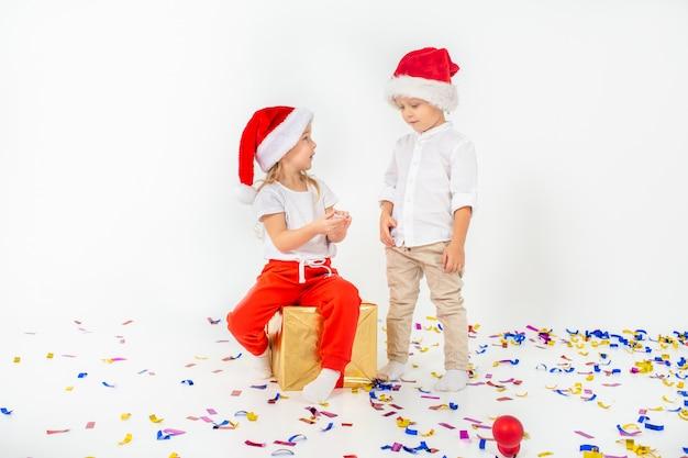 Zwei lustige kleinkinder in sankt-hut, der auf geschenkboxen sitzt. isoliert auf weißem hintergrund weihnachten und neujahr konzept.