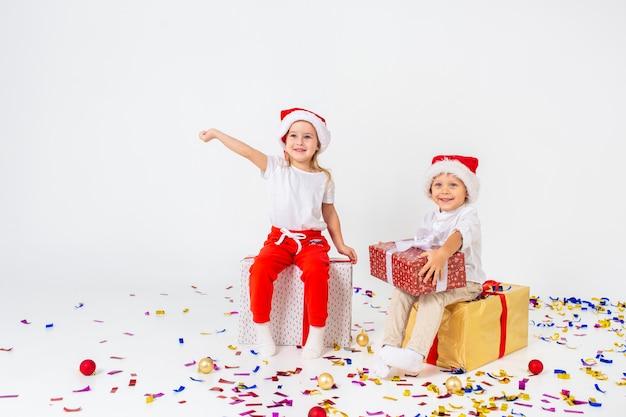 Zwei lustige kleinkinder in sankt-hut, der auf geschenkboxen sitzt