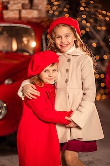 Zwei lustige mädchen auf der straße bei schneebedecktem wetter von einem roten auto in erwartung des neuen jahres