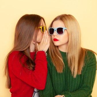 Zwei lustige schöne hippie-mädchen beim strickjacke- und sonnenbrillentrattern