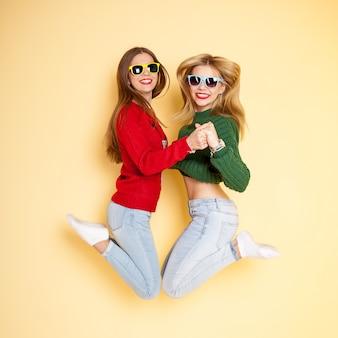 Zwei lustige schöne hippie-mädchen beim strickjacken- und sonnenbrillenspringen