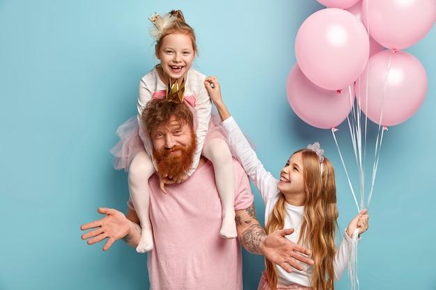 Zwei lustige ungezogene schwestern spielen zusammen und kitzeln sich gegenseitig, während sie von papa betreut werden. nettes kleines mädchen hält bündel luftballons. glückliche familie des vaters und zwei töchter bereiten sich auf urlaub vor, posieren drinnen