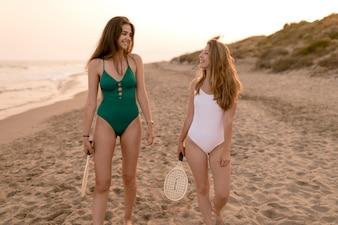 Zwei Mädchen, die auf den sandigen Strand hält Tennisschläger gehen