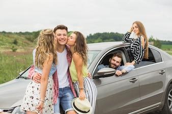 Zwei Mädchen, die ihren Freund steht nahe dem Auto küssen
