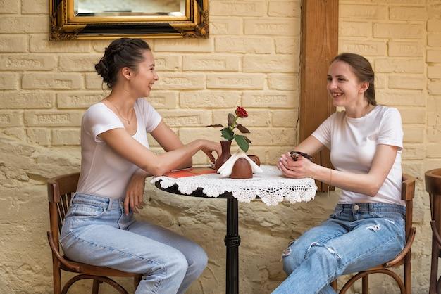 Zwei mädchen am runden tisch sprechen und lachen. freunde treffen, klatsch.