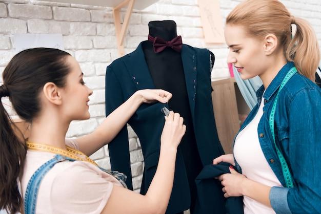 Zwei mädchen an der kleiderfabrik, die neue mannanzugsjacke desining ist.