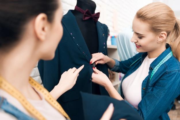 Zwei mädchen an der kleiderfabrik, die neue mannanzugsjacke desining ist