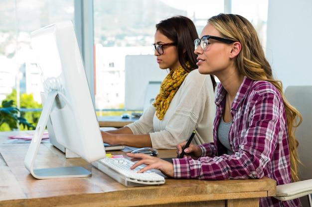 Zwei mädchen arbeiten im büro am computer und tablet