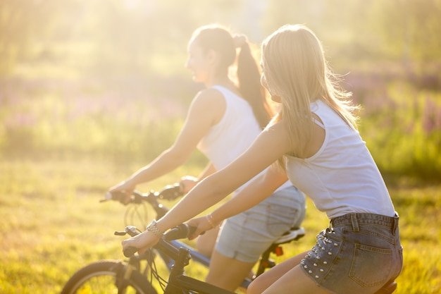 Zwei mädchen auf dem fahrrad bei sonnenaufgang