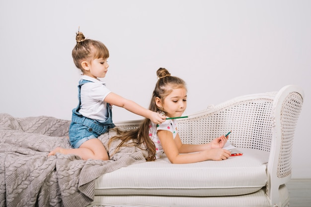 Zwei mädchen auf sofa mit bleistiften und papier