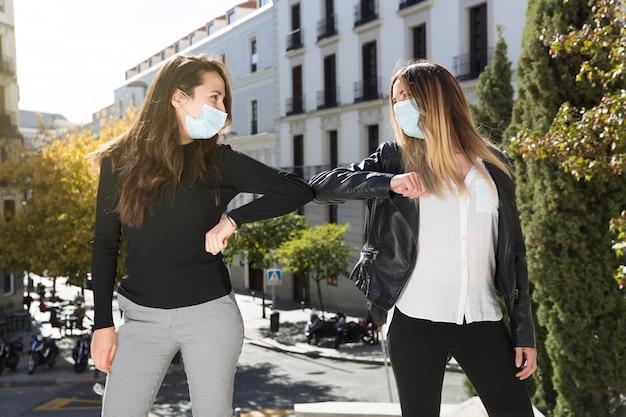 Zwei mädchen begrüßen sich mit ihren ellbogen. sie sind auf der straße und tragen op-masken. konzept der sozialen distanzierung und neuen normalität.