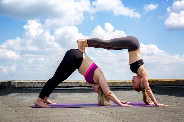 Zwei mädchen beschäftigen sich mit akro-yoga