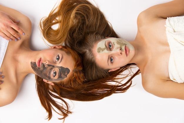 Zwei mädchen, blond und rothaarig, freundinnen mit verschiedenen masken auf dem halben gesicht, in handtüchern gewickelt auf dem boden liegend. gesundes haut- und schönheitskonzept auf weißer wand. hochwertiges foto