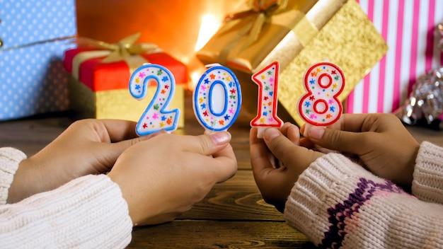 Zwei mädchen, die 2018 zahlen auf kerzen neben bunten geschenken und weihnachtsgeschenken halten