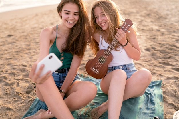 Zwei mädchen, die am strand nimmt selbstporträt sitzen