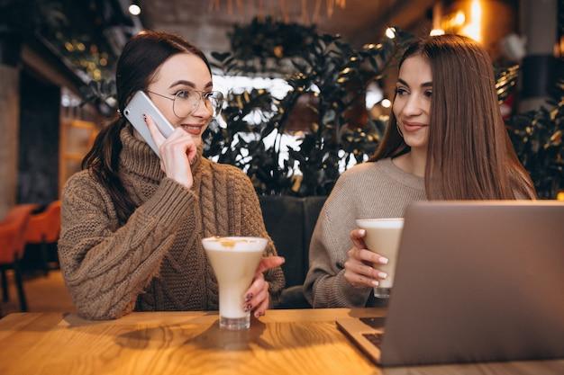 Zwei mädchen, die an einem computer in einem café arbeiten