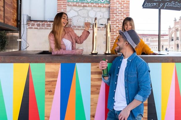 Zwei mädchen, die an einer bar im freien arbeiten, stoßen an und feiern mit einem kunden