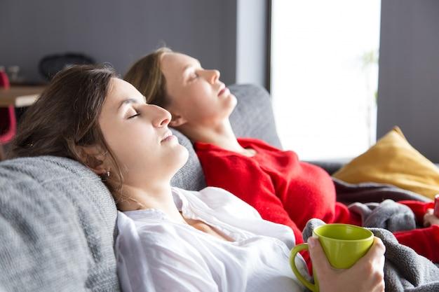 Zwei mädchen, die auf couch stillstehen