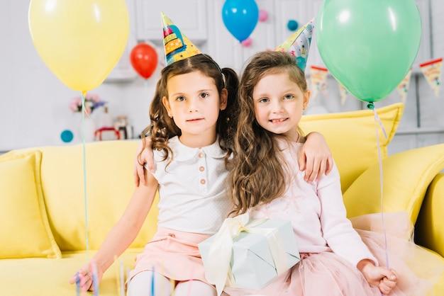 Zwei mädchen, die auf dem gelben sofa sitzen gelbe und grüne ballone in den händen sitzen