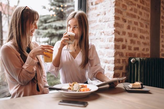 Zwei mädchen, die auf tablette in einem café kaufen