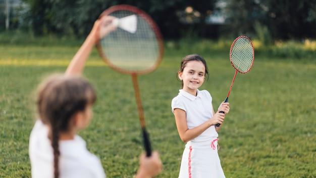 Zwei mädchen, die badminton im park spielen