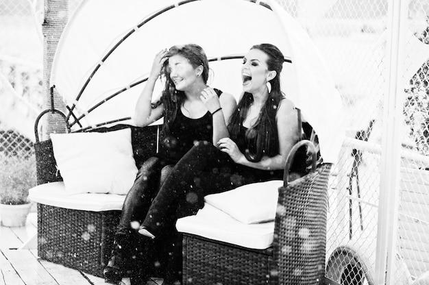 Zwei mädchen, die bei regen auf der couch sitzen und laut lachen