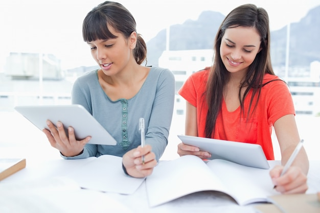 Zwei mädchen, die beide tablet-pcs verwenden, um ihre hausaufgaben zu machen