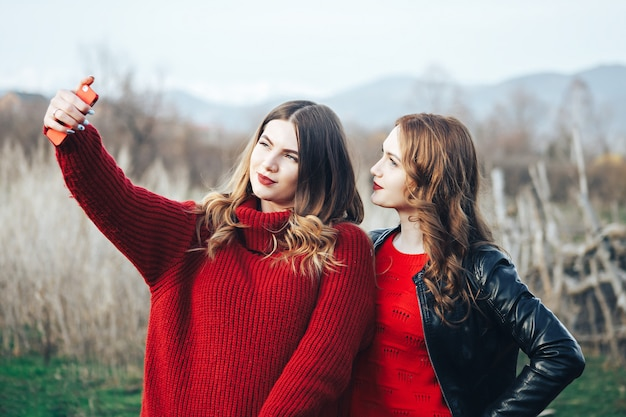 Zwei mädchen, die das selfie im freien machen