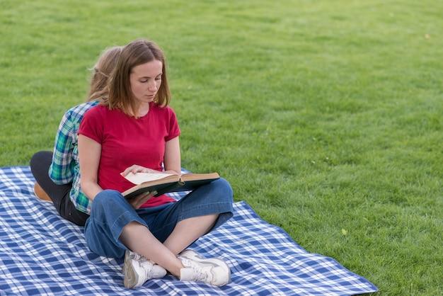 Zwei mädchen, die draußen auf picknickdecke studieren