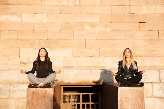Zwei mädchen, die draußen bei sonnenuntergang yoga praktizieren. platz für text.