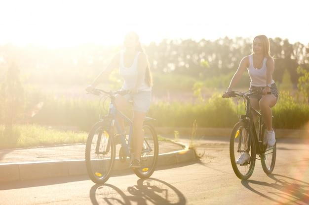 Zwei mädchen, die ein fahrrad in einem schönen tag reiten