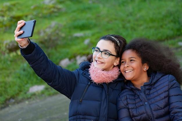 Zwei mädchen, die ein foto mit dem mobile machen