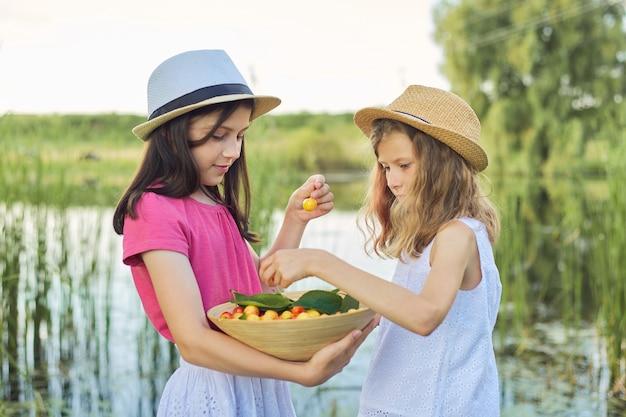 Zwei mädchen, die gelbe kirschen essen, sommertag in der natur