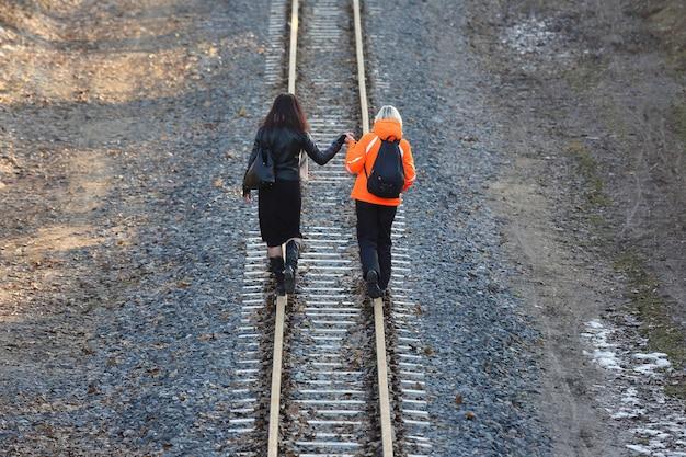 Zwei mädchen, die hände halten, die auf der eisenbahn gehen