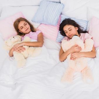 Zwei mädchen, die in der hand den teddybären zusammen schlafen auf bett halten