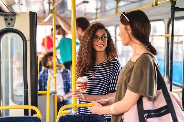 Zwei mädchen, die in einem bus stehen, der plaudert und kaffee trinkt.