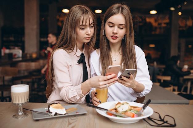 Zwei mädchen, die in einem café mit telefon zu mittag essen