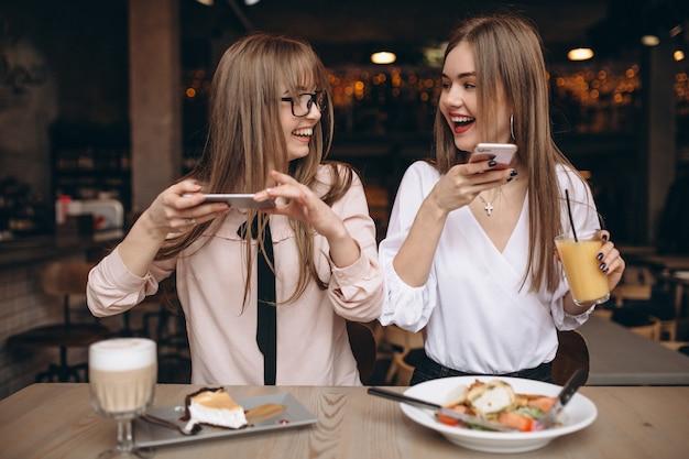 Zwei mädchen, die in einem café zu mittag essen und fotos machen