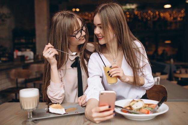 Zwei mädchen, die in einem café zu mittag essen und selfie tun