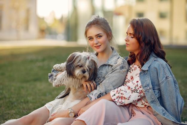 Zwei mädchen, die in einem park mit einem kleinen hund sitzen