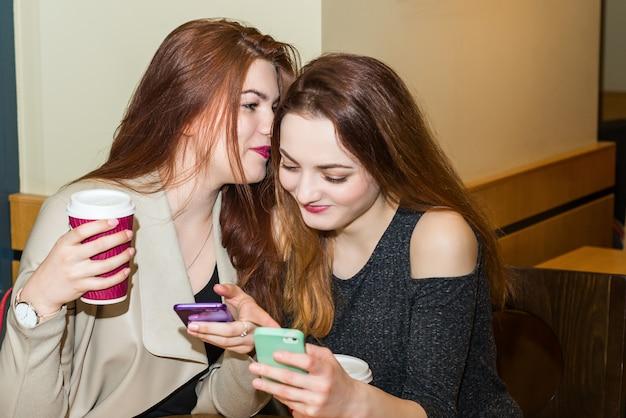 Zwei mädchen, die in einer caféstange klatschen