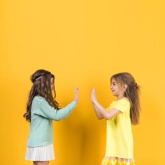 Zwei mädchen, die klatschende hände spielen