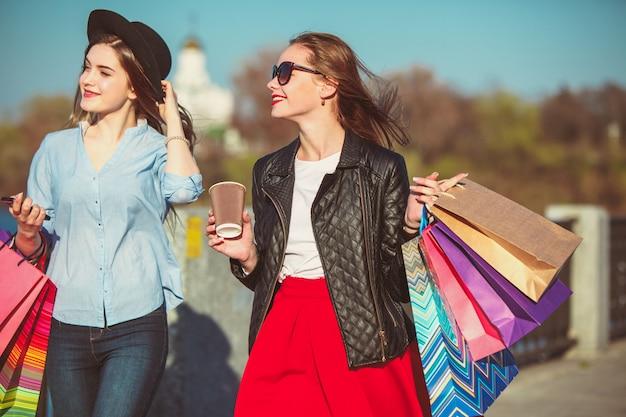 Zwei mädchen, die mit dem einkaufen auf stadtstraßen gehen