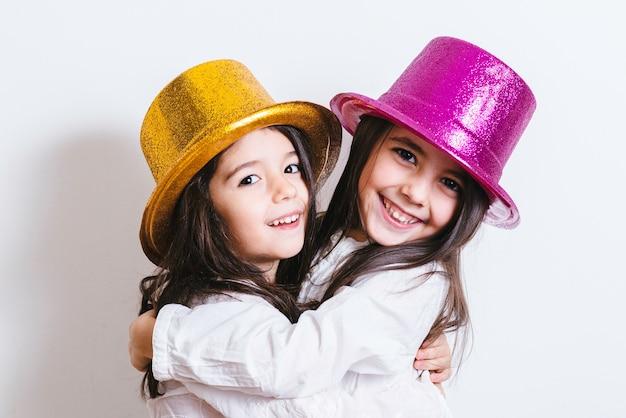 Zwei mädchen, die mit den gelben und rosa glänzenden hüten aufwerfen