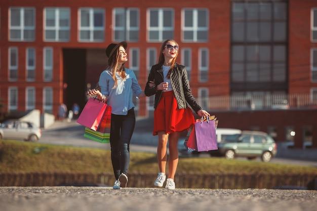 Zwei mädchen, die mit einkaufstüten auf stadtstraßen am sonnigen tag gehen