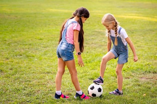 Zwei mädchen, die mit fußball auf gras spielen