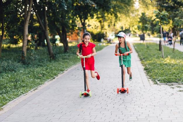 Zwei mädchen, die reiten genießen, stoßen roller im park